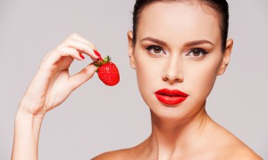Sweet temptation. Beautiful young shirtless woman holding strawberry in her hand while standing against grey background